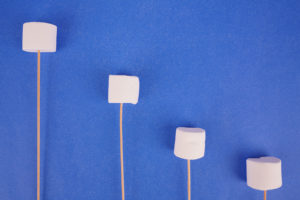 Fluffy marshmallows with sticks on blue background