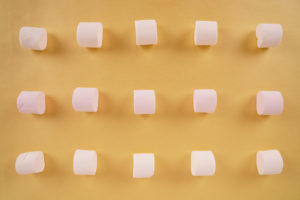 Pattern with marshmallow candies on yellow stock photo