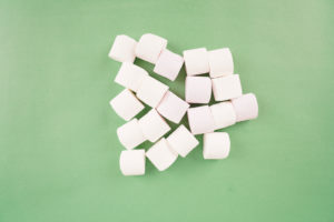 White marshmallow on green stock photo